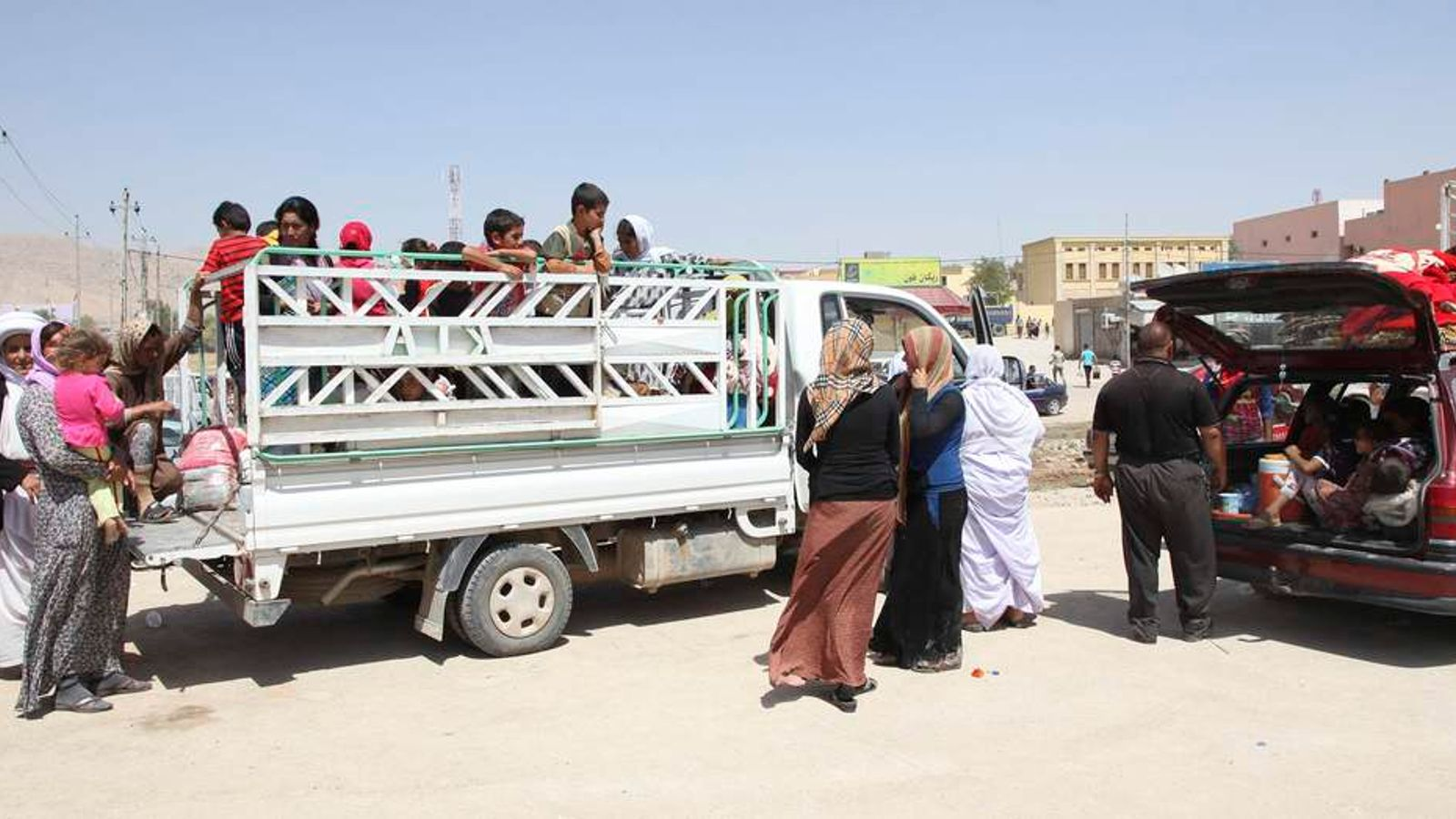 Displaced families from the minority Yazidi sect, fleeing the violence in the Iraqi town of Sinjarl west of Mosul, arrive at Dohuk province