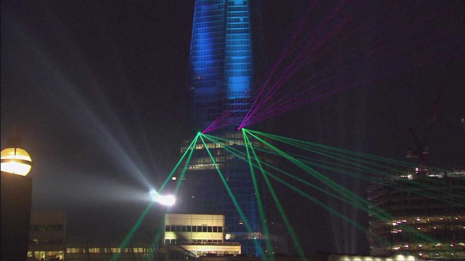 Purple and green lasers dart across the London Sky as the shard is in blue