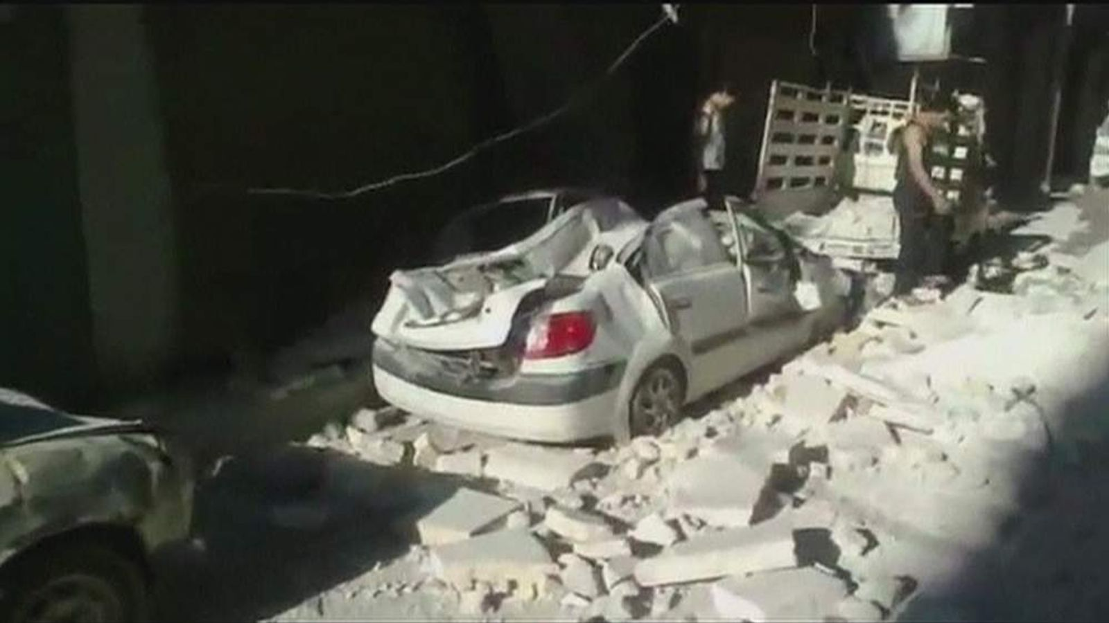Rubble covers a destroyed car in Aleppo