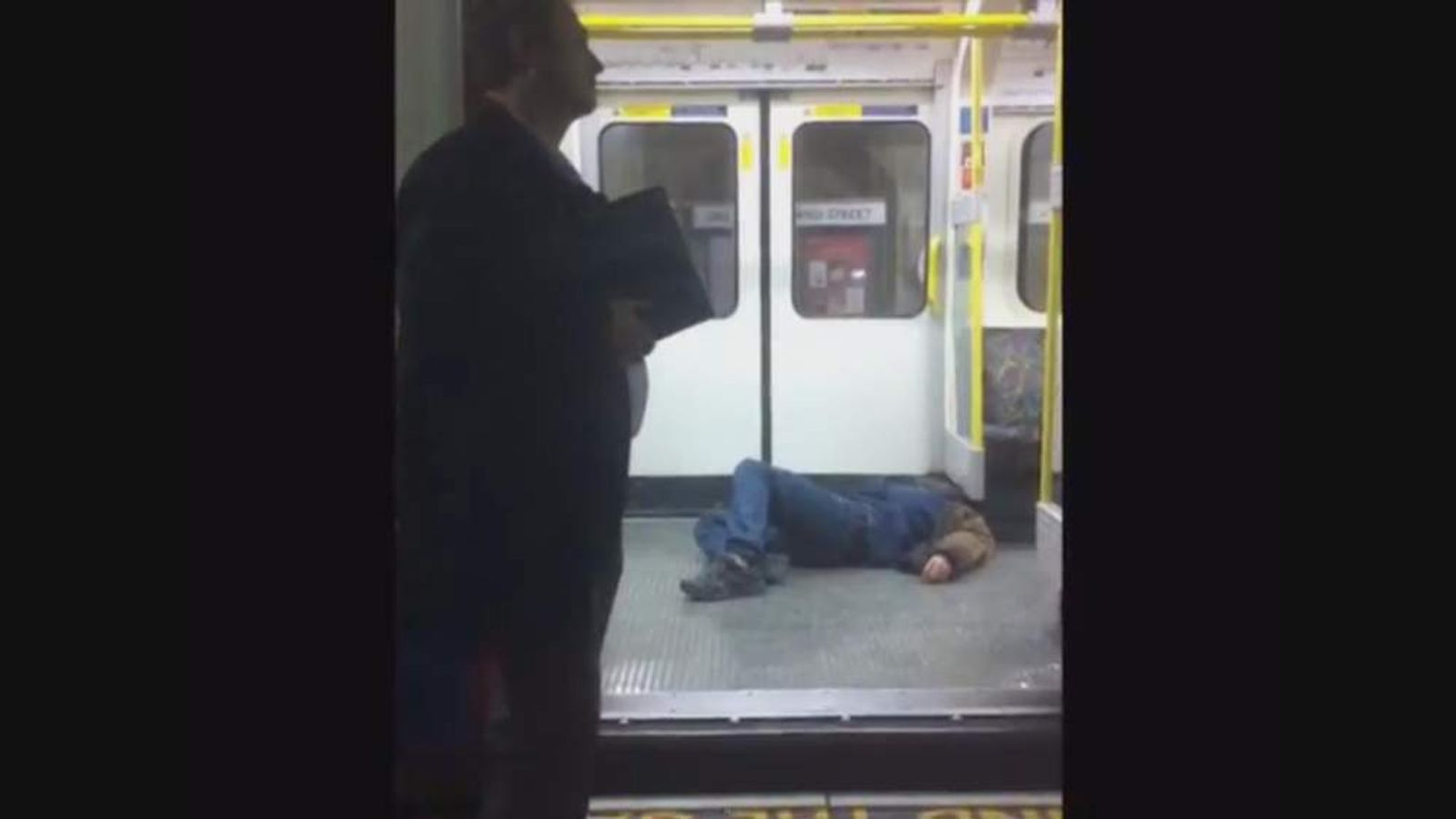 A man lies collapsed on the floor of the tube