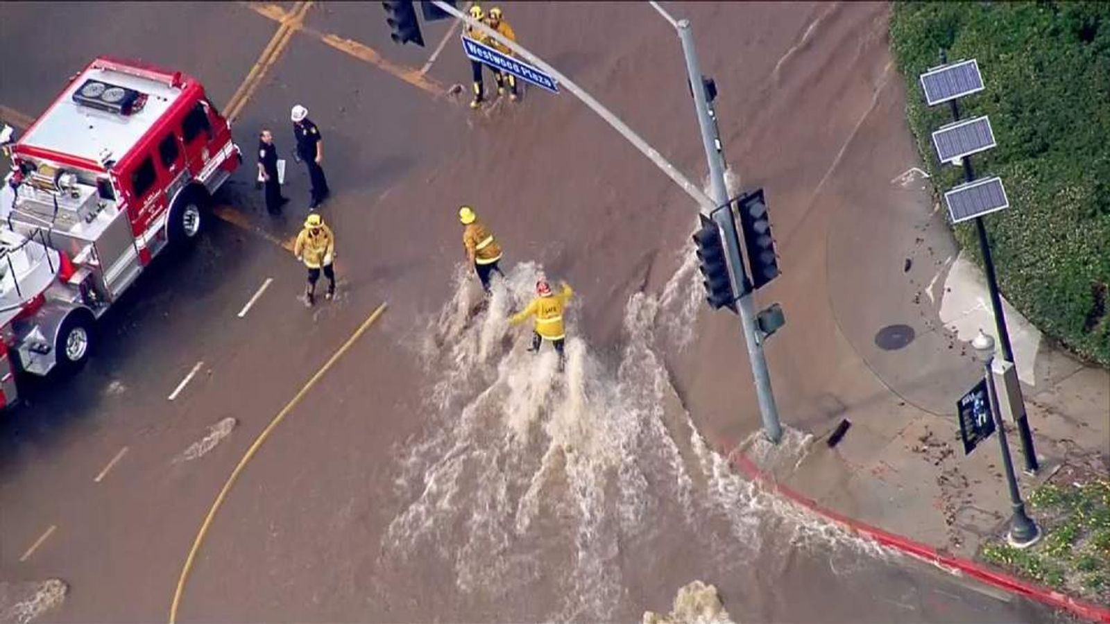 Firefighters struggle to stay upright amid the deluge