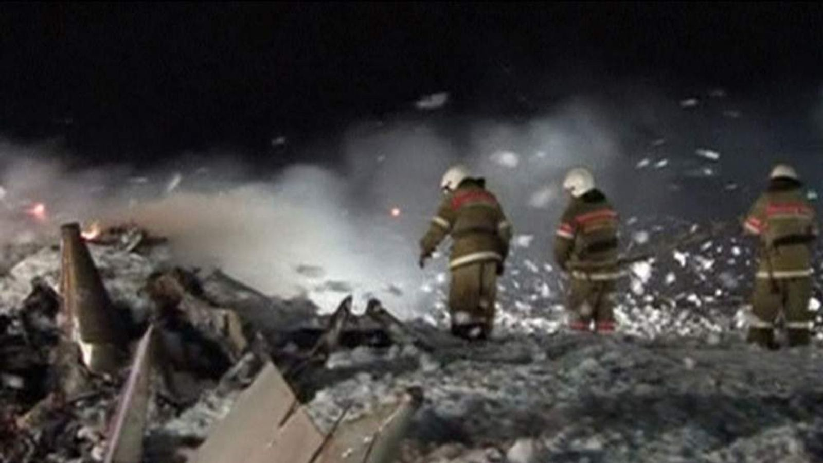 Firefighters out out the blaze at the scene of a plane crash in Russia