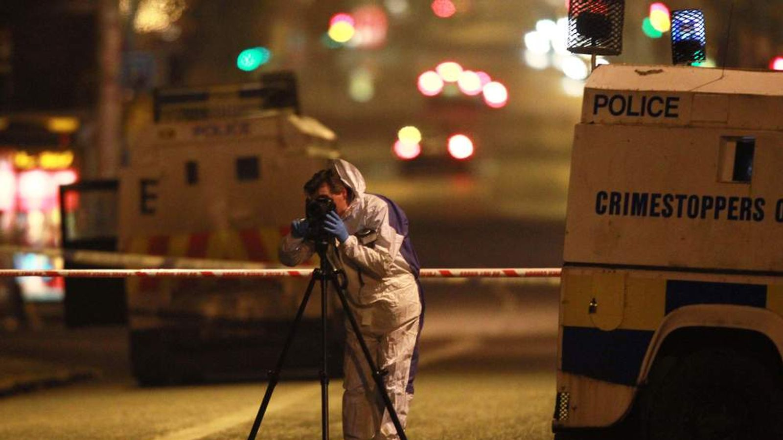A forenics photographer photographs a burnt police patrol car outside Alliance Party MP Naomi Long's office in east Belfast