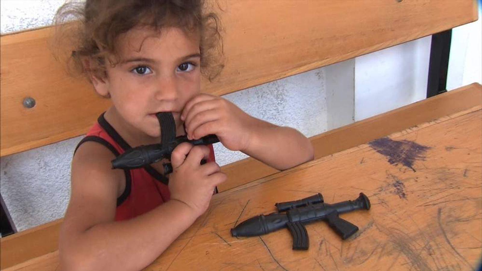 A youngster plays with a toy gun in a play camp in Gaza
