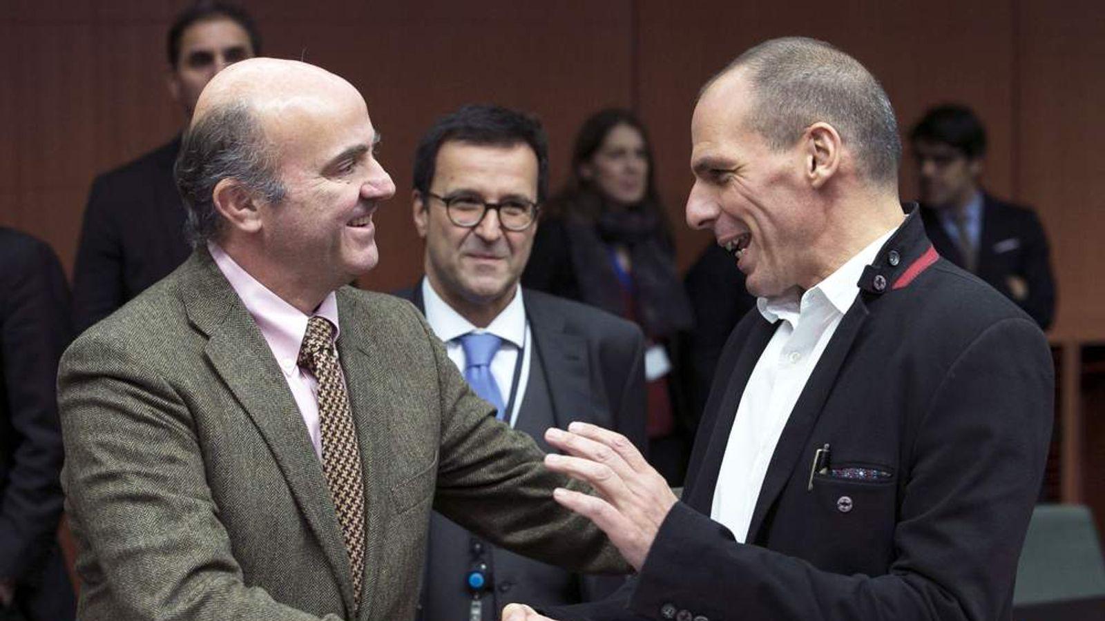 Luis de Guindos (L) talks with Yanis Varoufakis