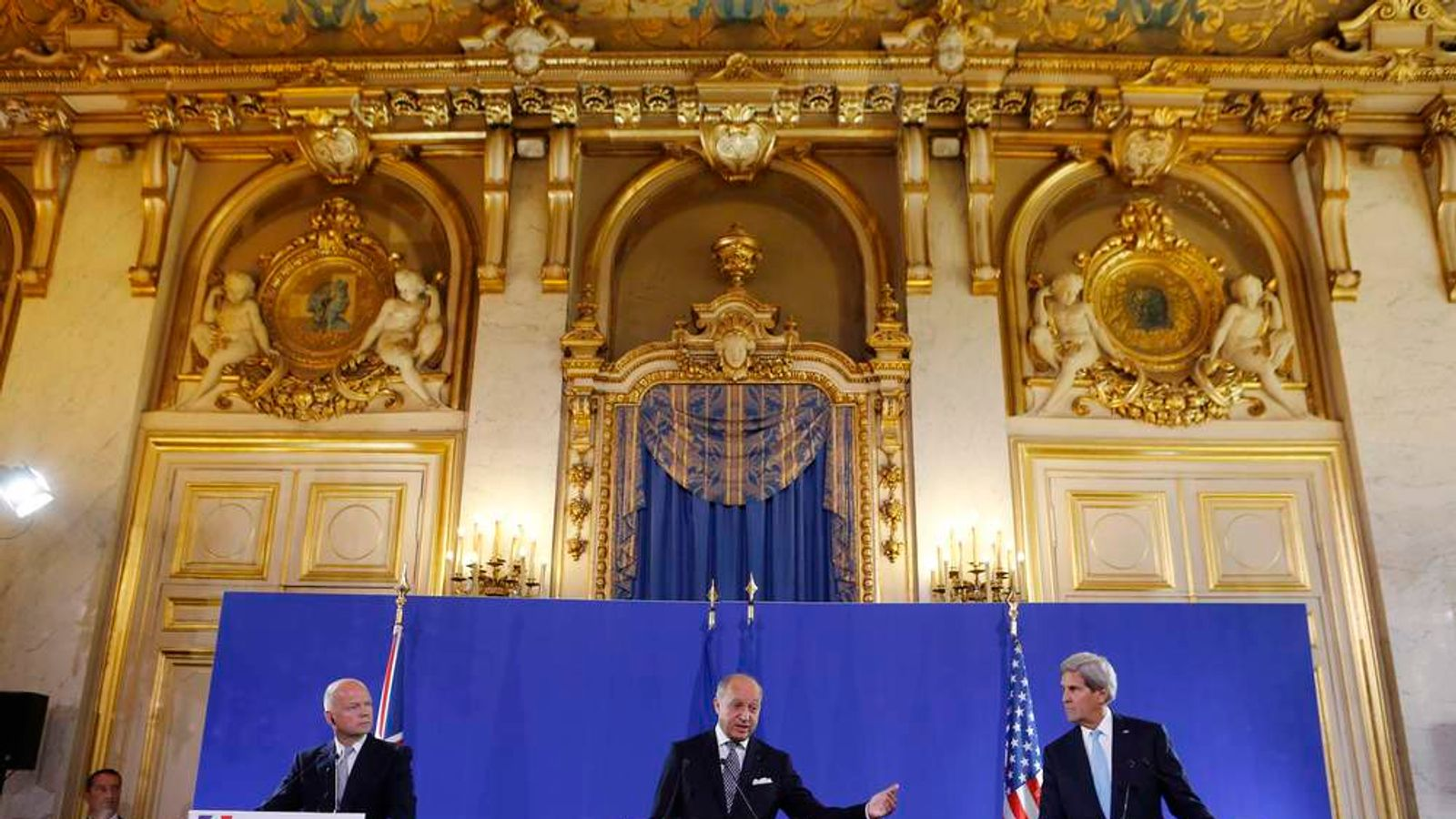 U.S. Secretary of State Kerry and British Foreign Secretary Hague listen to French FM Fabius speak at a news conference at the Quai d'Orsay in Paris