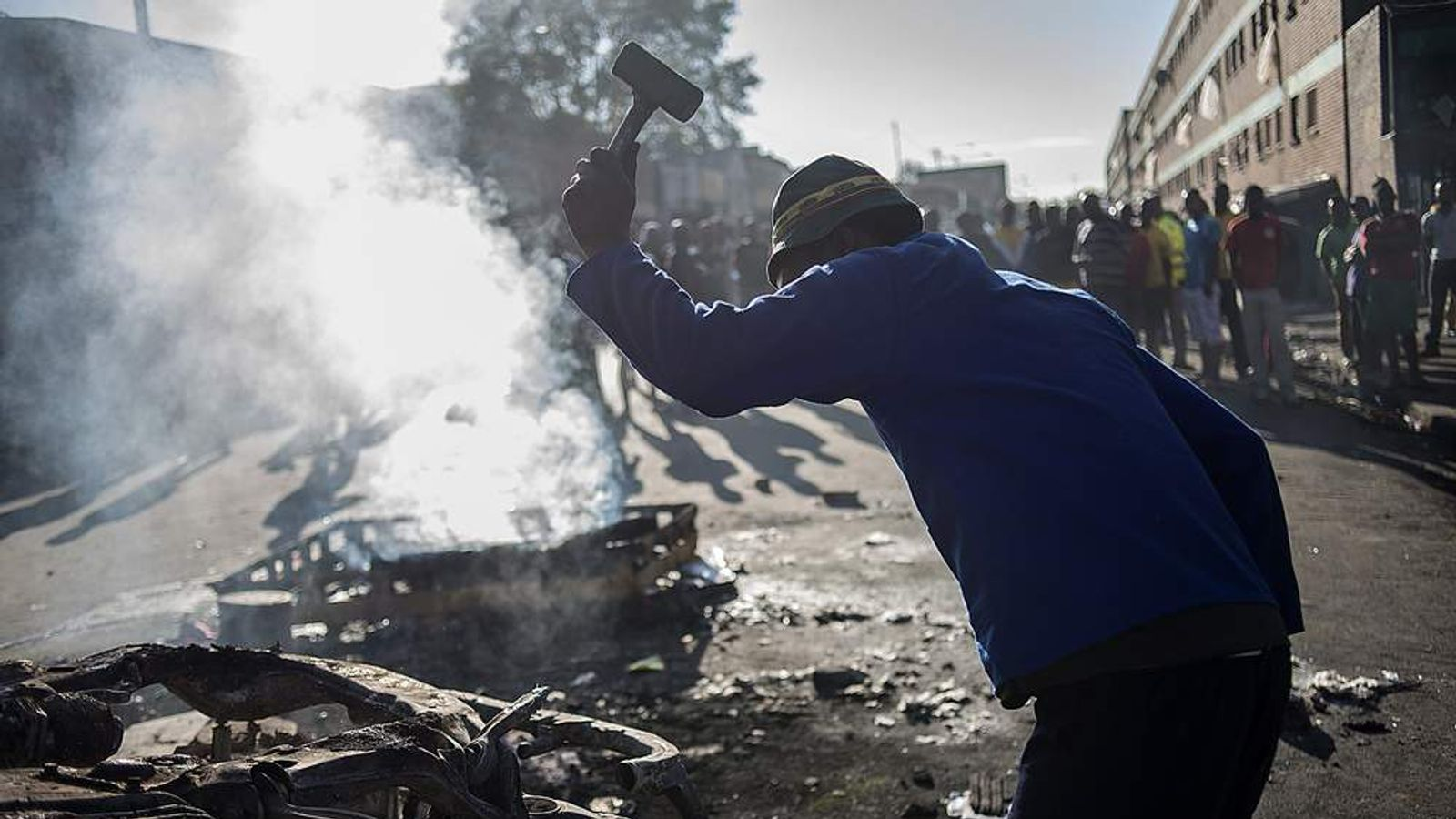 A man retrieves metal scraps from a burnt-out car