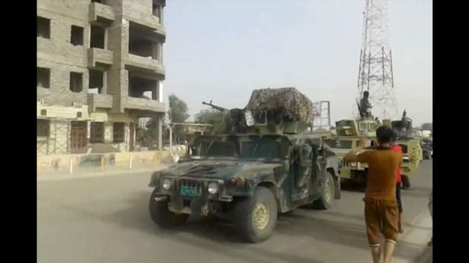 ISIS militants parade through the city of Baiji