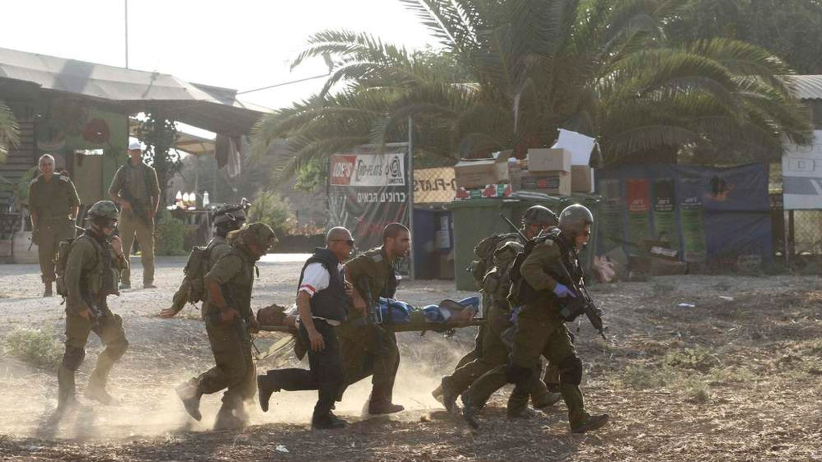 Israeli soldiers evacuate wounded comrade from the scene outside the central Gaza Strip