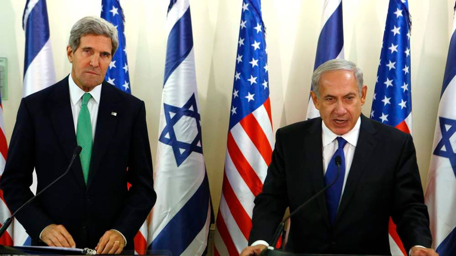 U.S. Secretary of State Kerry listens as Israel's Prime Minister Netanyahu speaks to the media at the prime minister's office in Jerusalem