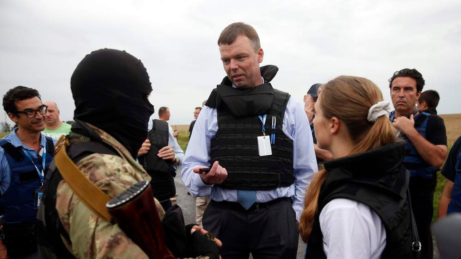 OSCE monitors speak with a pro-Russian separatist at the site of Thursday's Malaysia Airlines Flight MH17 plane crash near the settlement of Grabovo