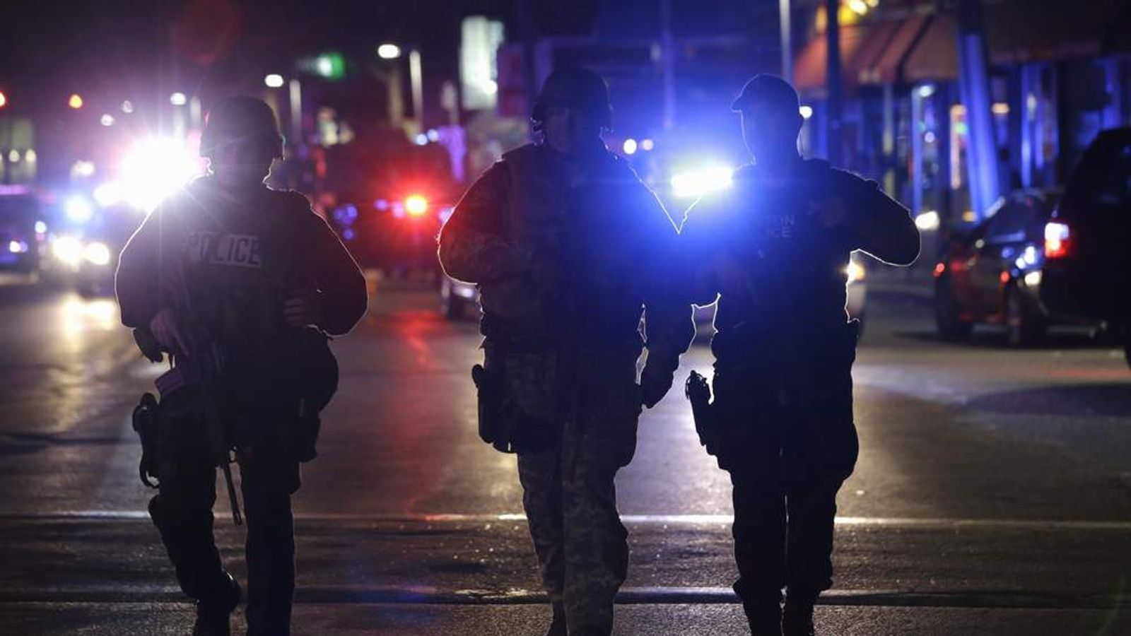 Officers wearing tactical gear arrive at the Watertown neighborhood of Boston