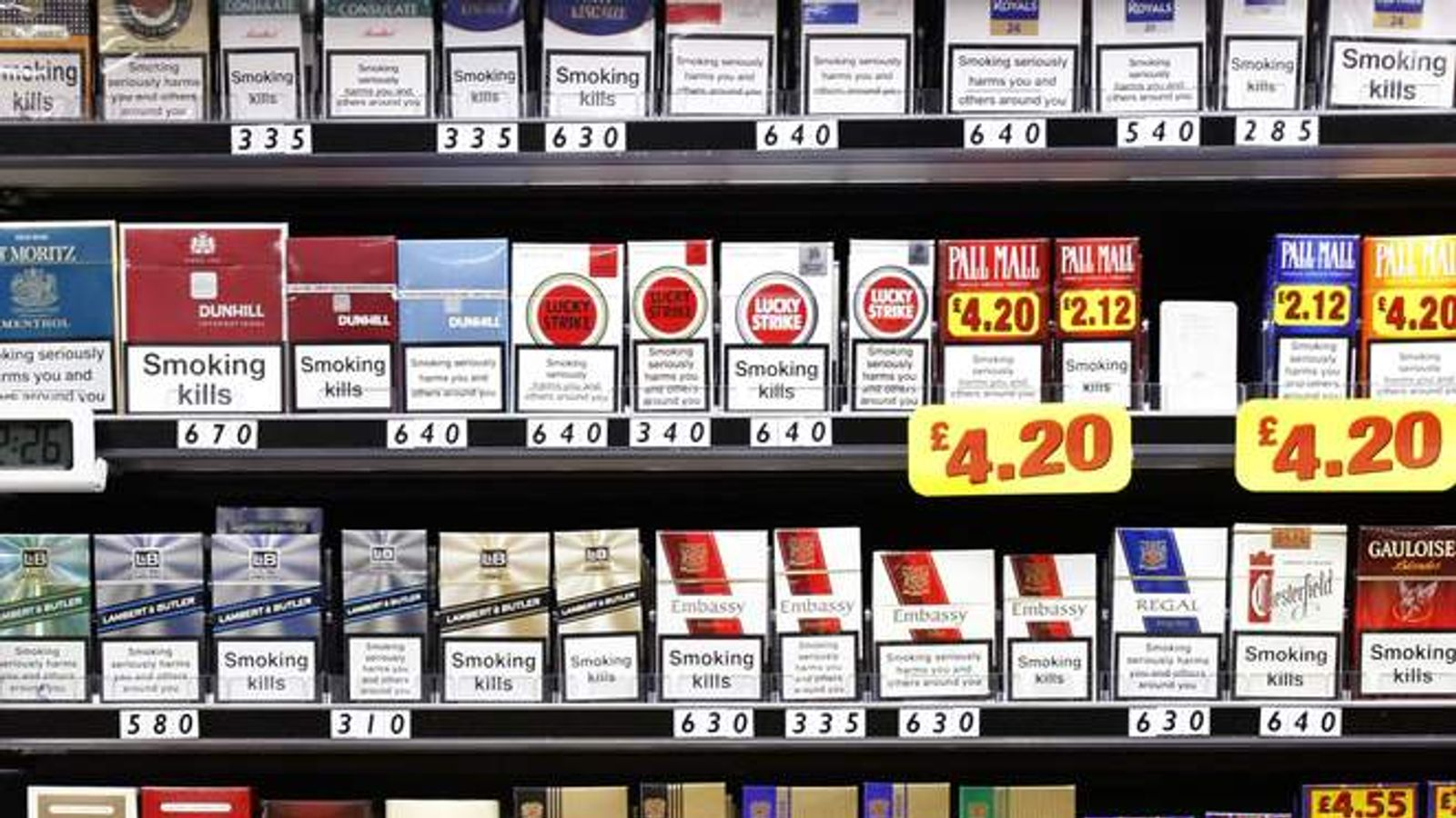 Shopkeeper Picking Cigarettes Off Shelf In Shop