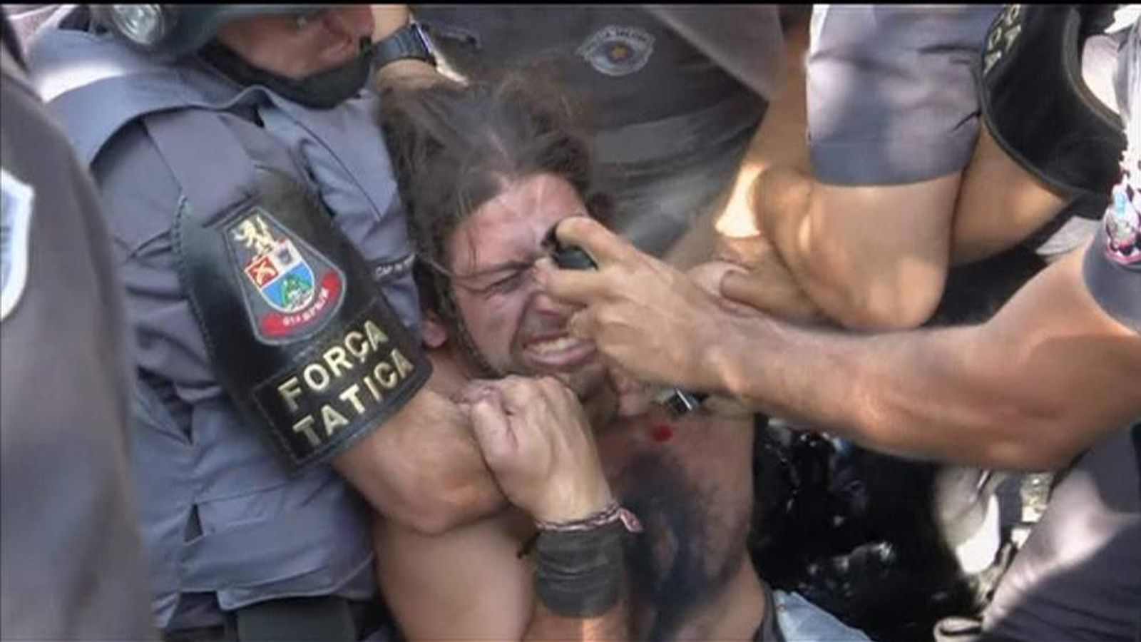 Brazilian police restrain a Sao Paulo protester before pepper spraying him