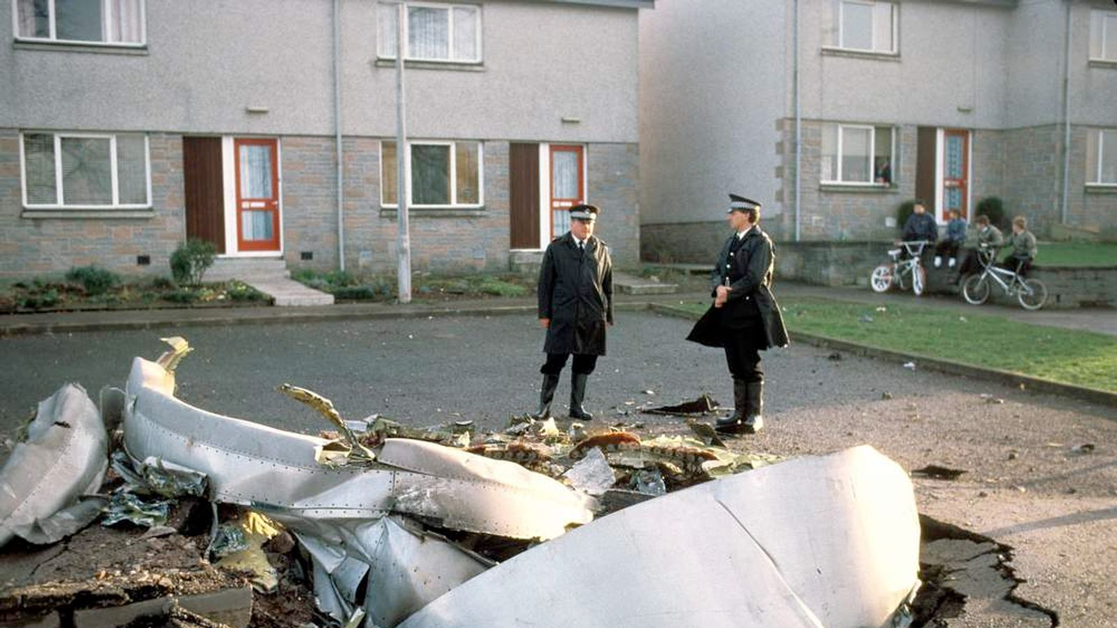Police officers standing among debris in the Scottish town of Lockerbie after a Pan Am jumbo jet exploded mid-air and crashed in flames on to the market town
