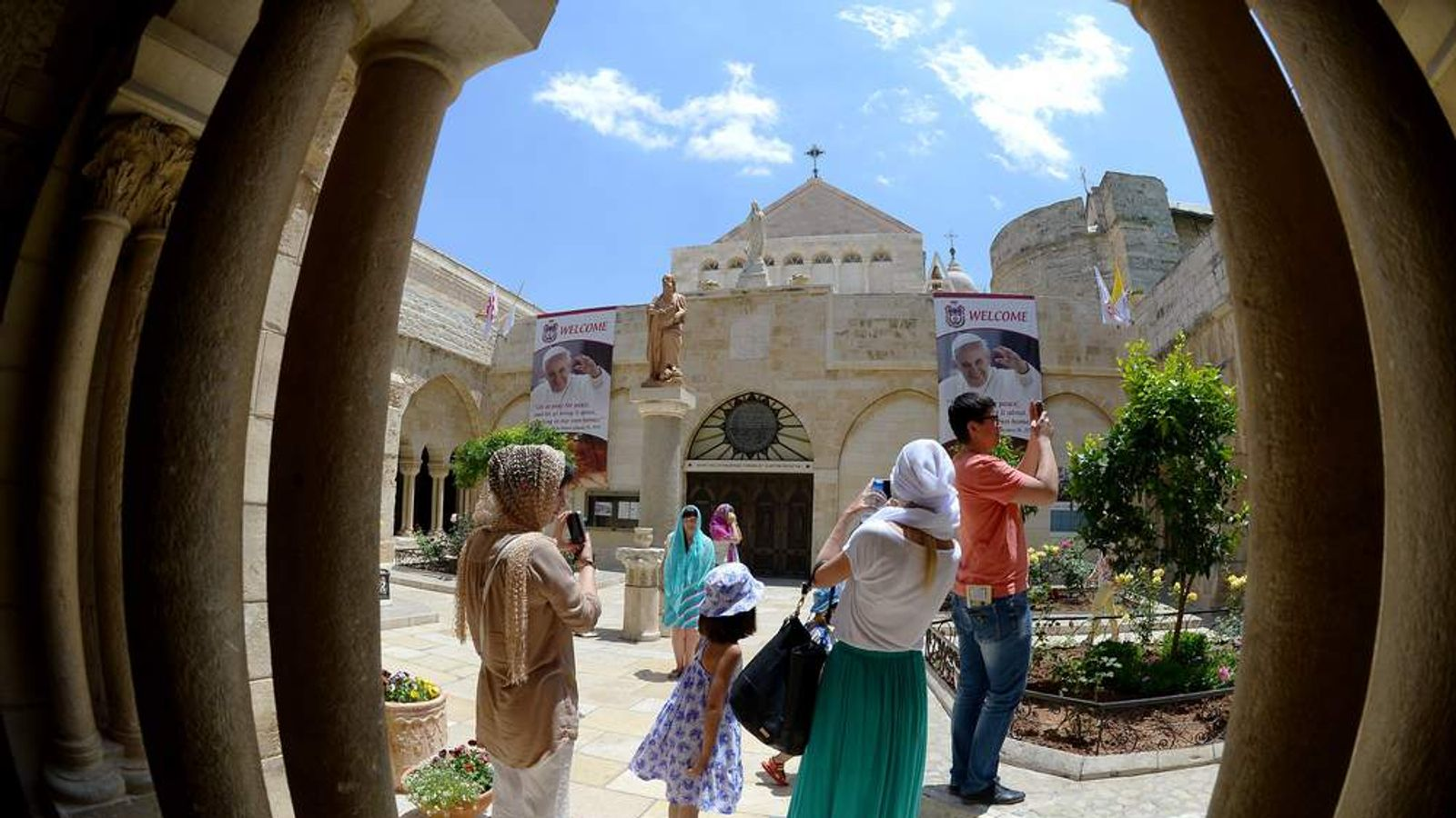 Pilgrims take photos in the courtyard of the Church of the Nativity in Bethlehem