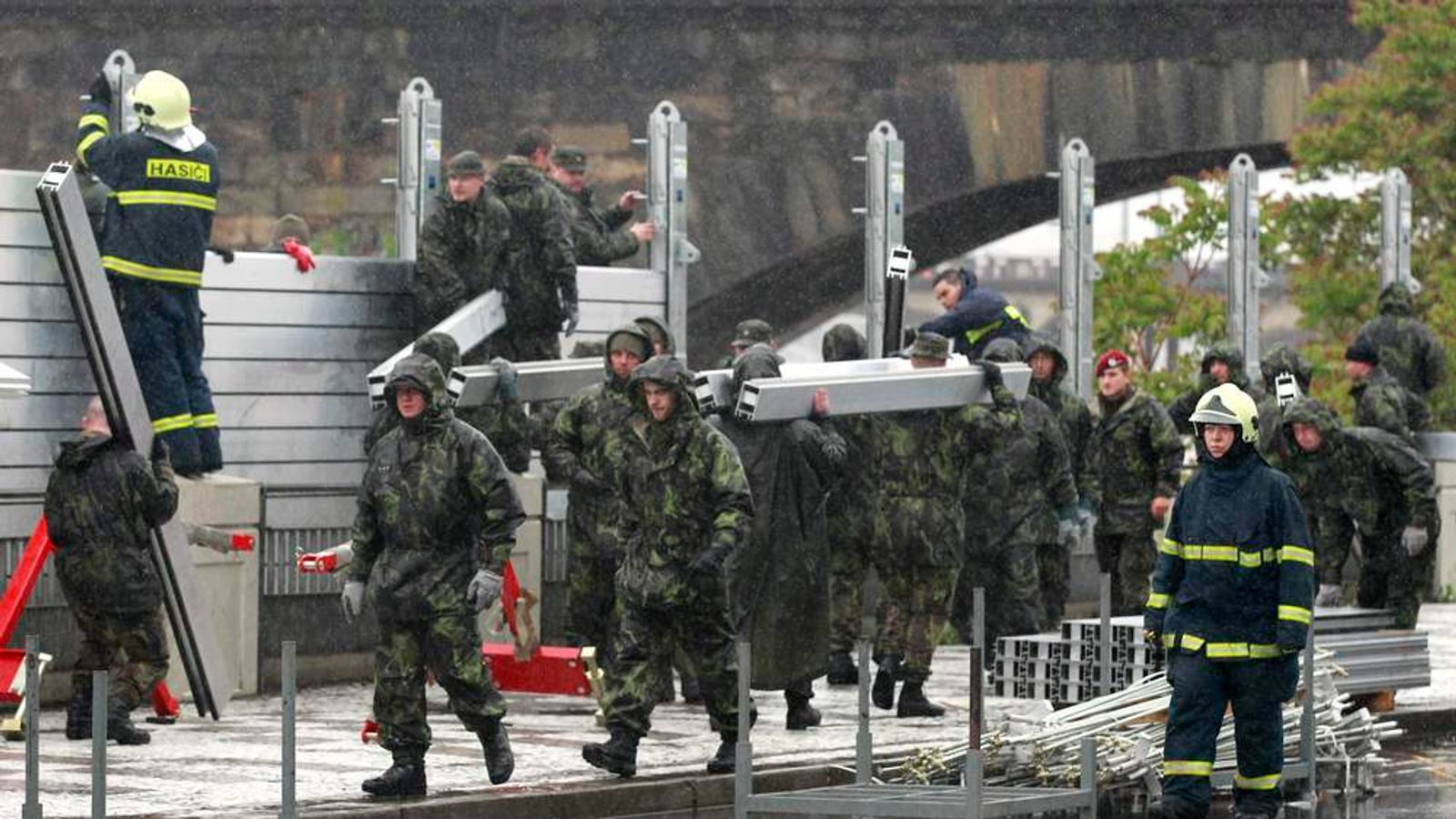 Czech soldiers erect metal barriers at a bank of Vltava river in Prague's Holesovice district.