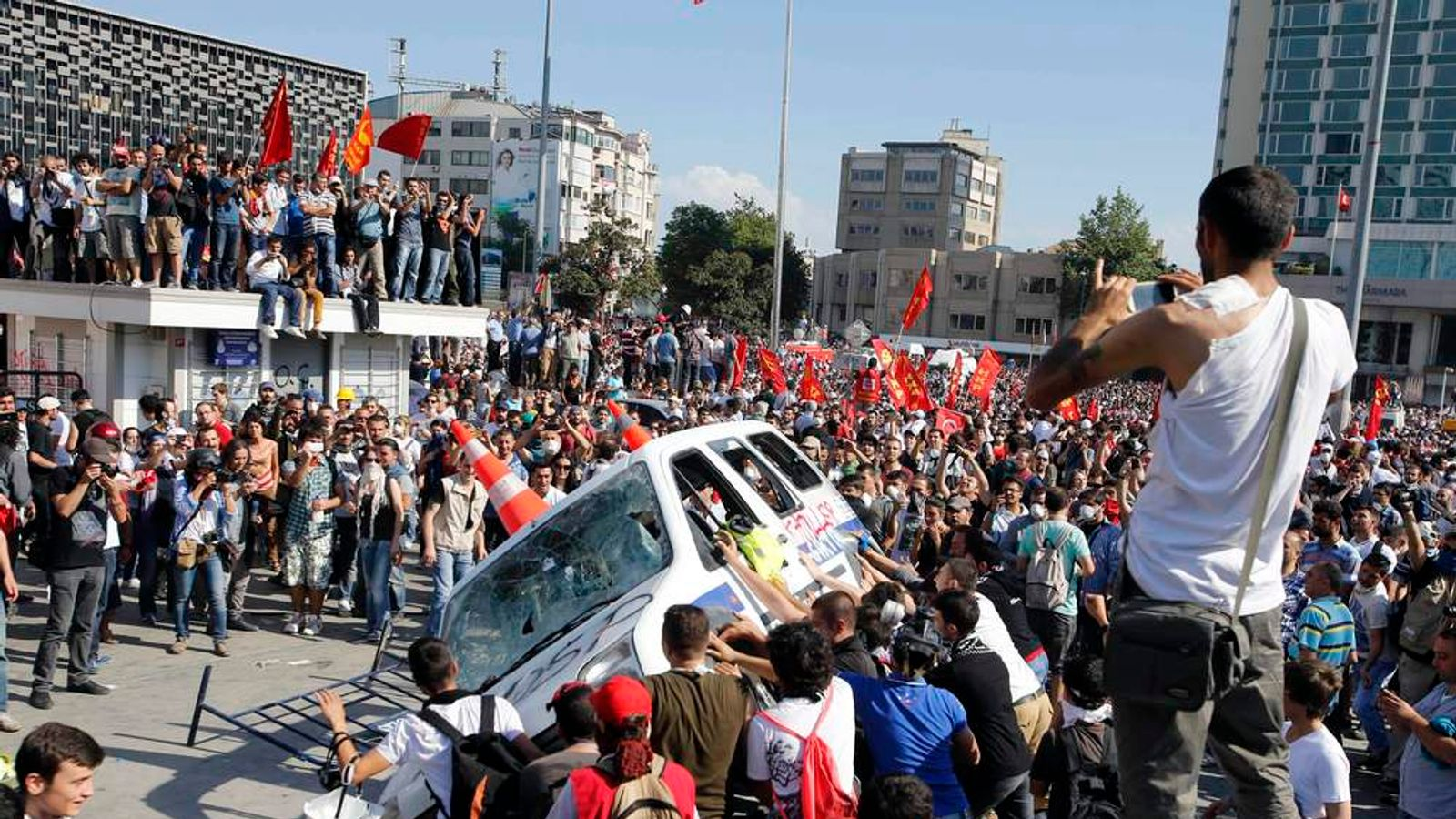 Protesters prepare to roll a police car over during an anti-government protest at Taksim Square