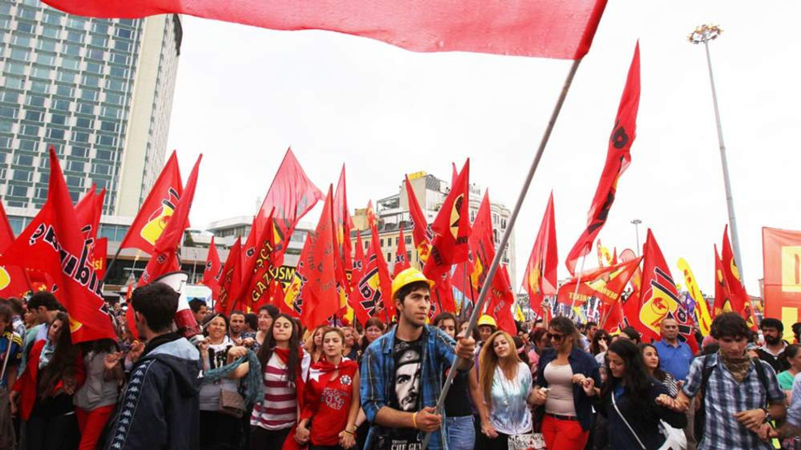 Protesters wave flags as others dance during the third day of nationwide anti-government protest at the Taskim square in Istanbul