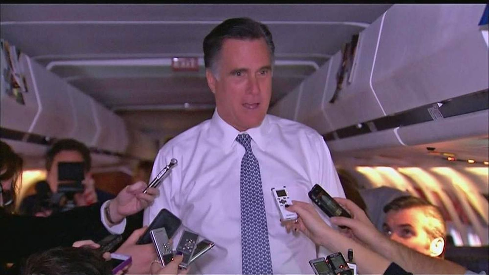 Mitt Romney talks to reporters on his campaign plane