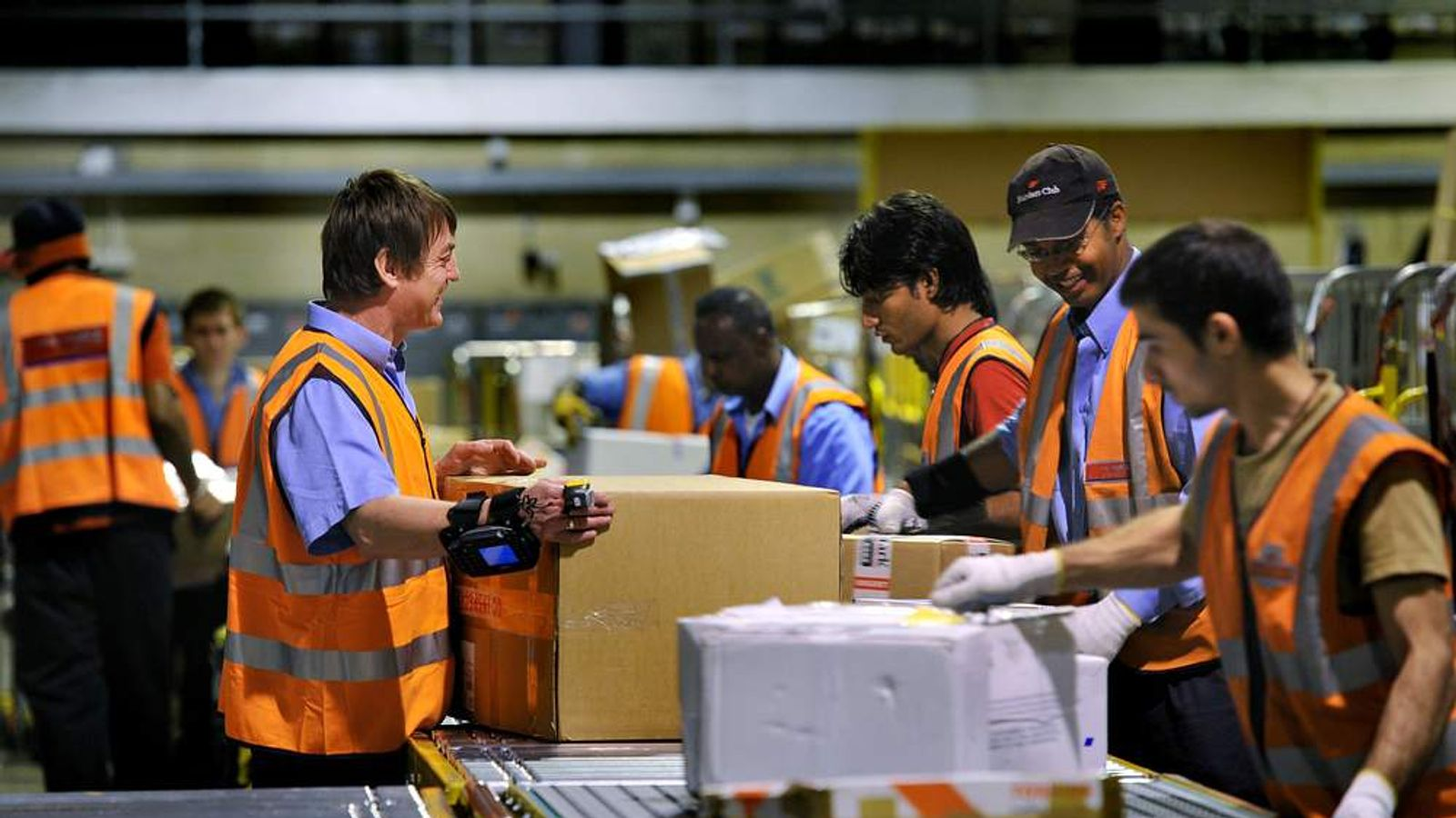 Royal Mail staff sort parcels at central distribution centre