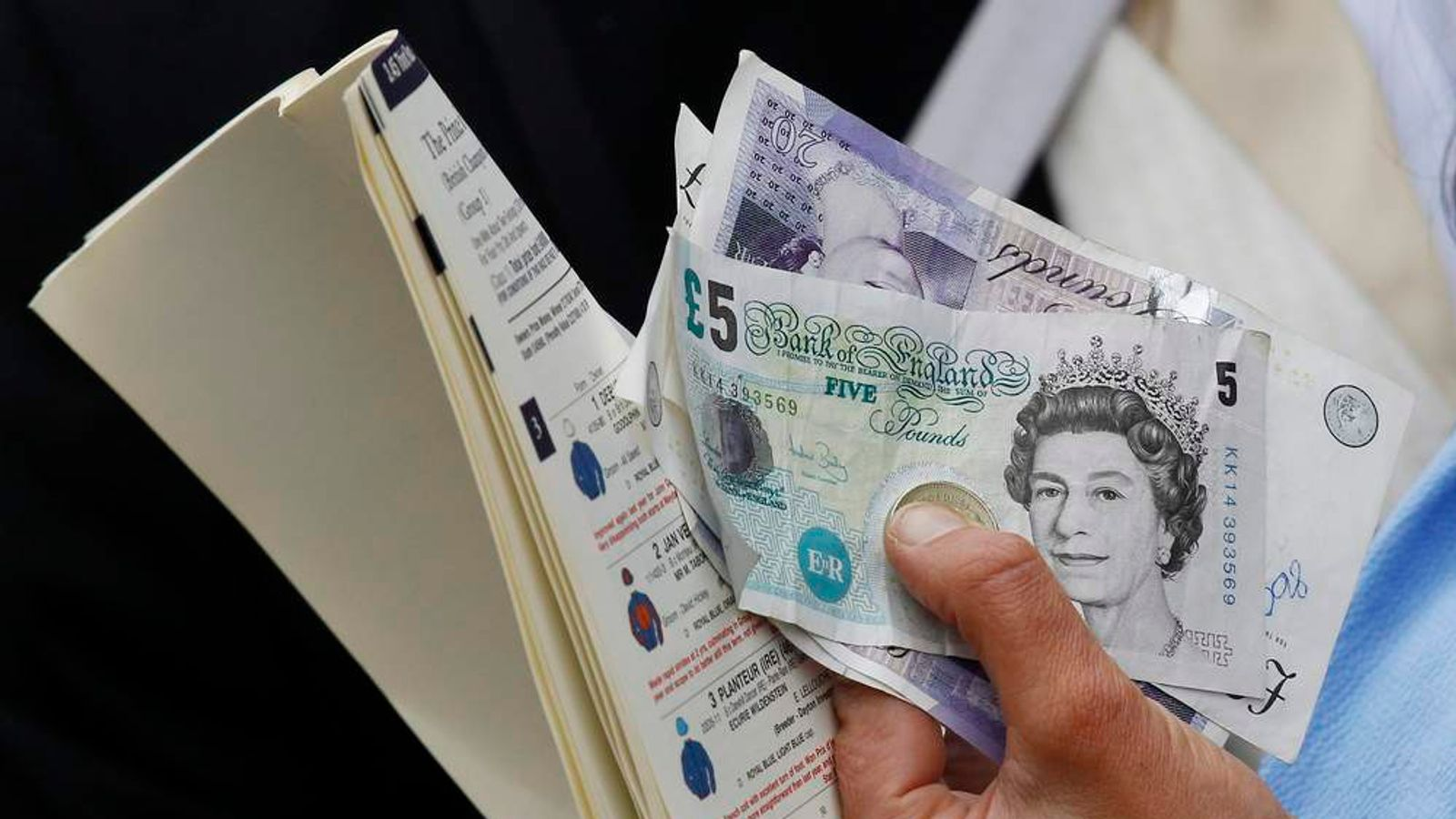A woman holds her money and her racing programme as she queues to make a bet on the second day of racing at Royal Ascot in southern England