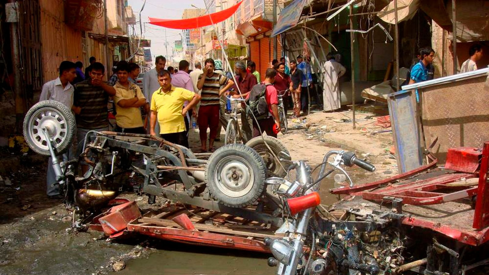 Residents look at damaged vehicles at the site of a bomb attack in a market in Diwaniya, 150 km south of Baghdad