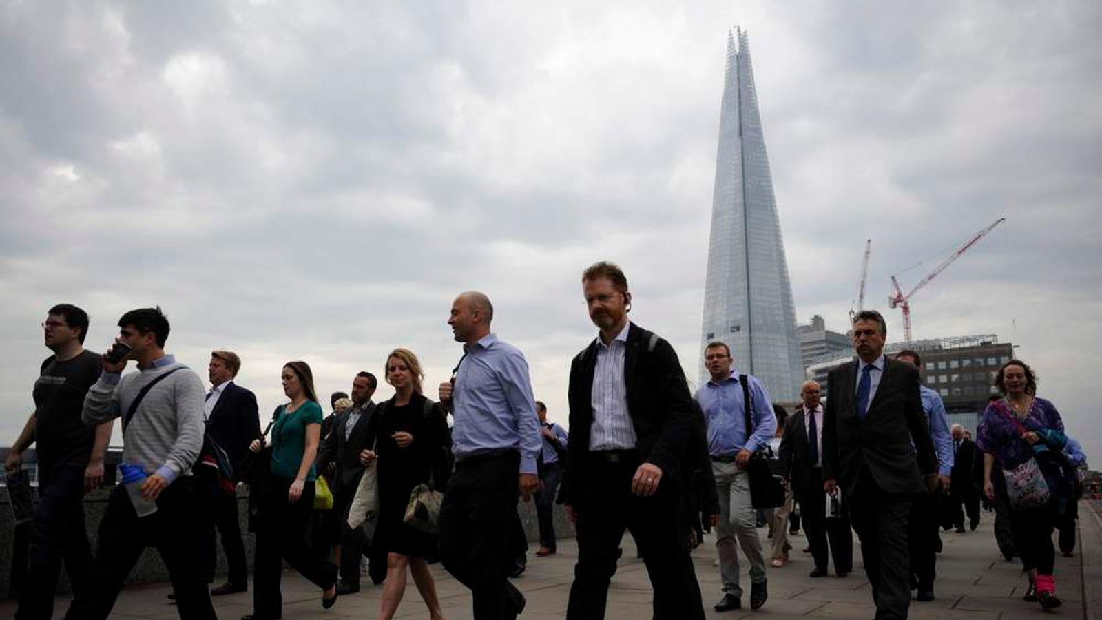 Commuters walk towards the financial district via London Bridge
