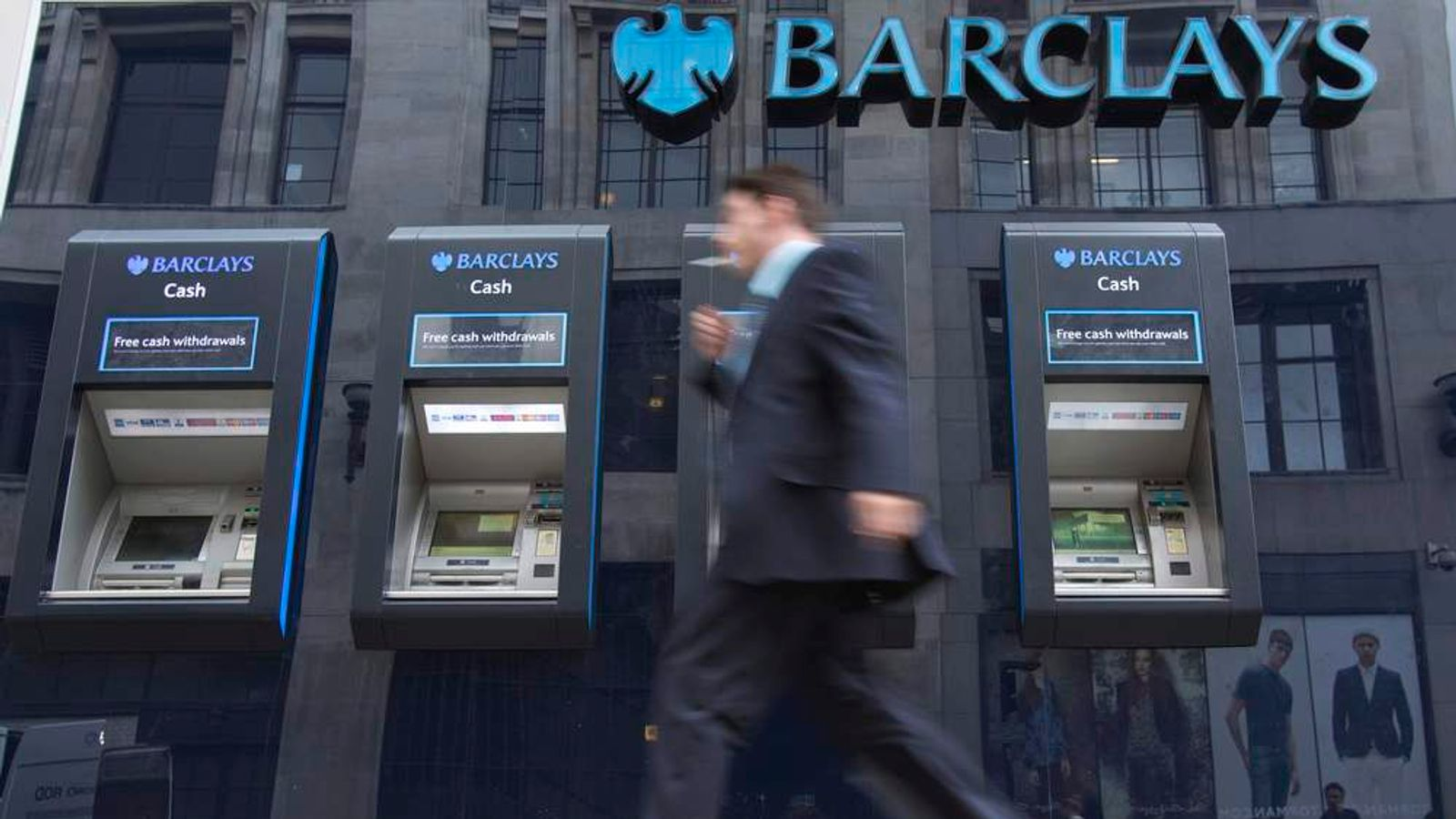A man passes automated teller machines at a Barclays bank branch in London