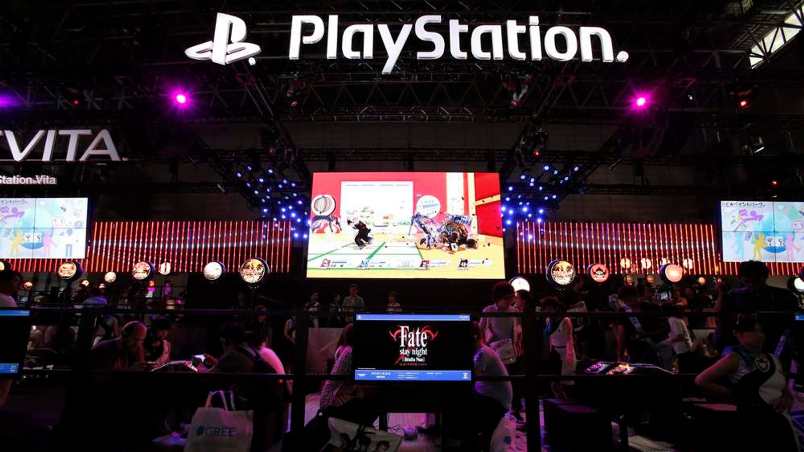 Visitors try out new game software on Sony's PlayStation Vita handheld gaming device at Tokyo Game Show in Chiba