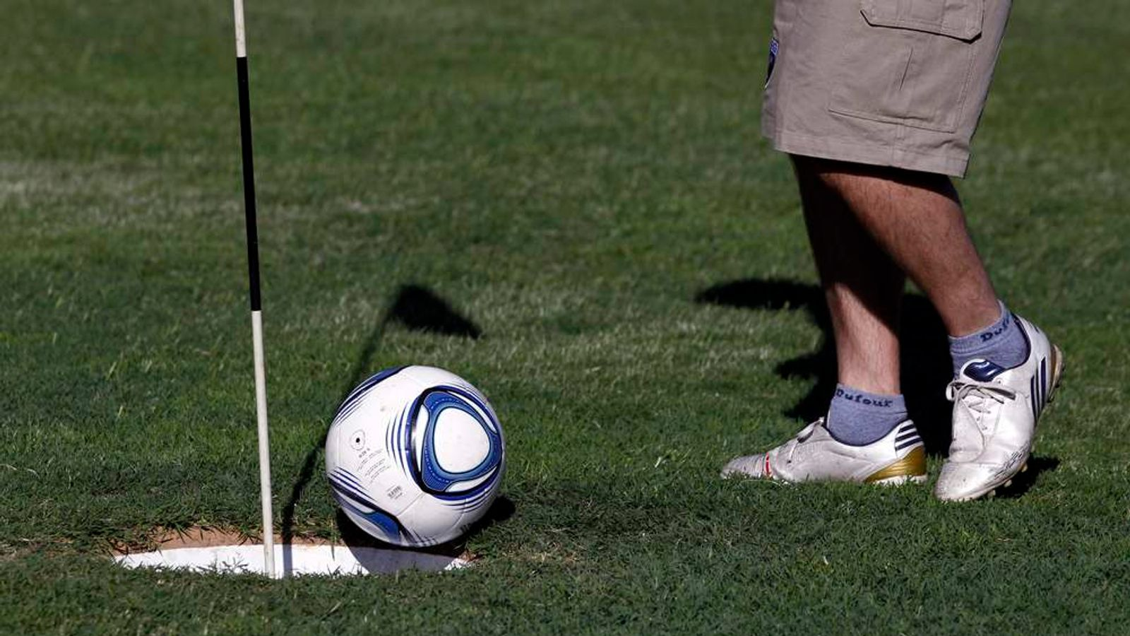 A man kicks a ball into the hole as he competes in a FootGolf tournament on the outskirts of Buenos Aires.