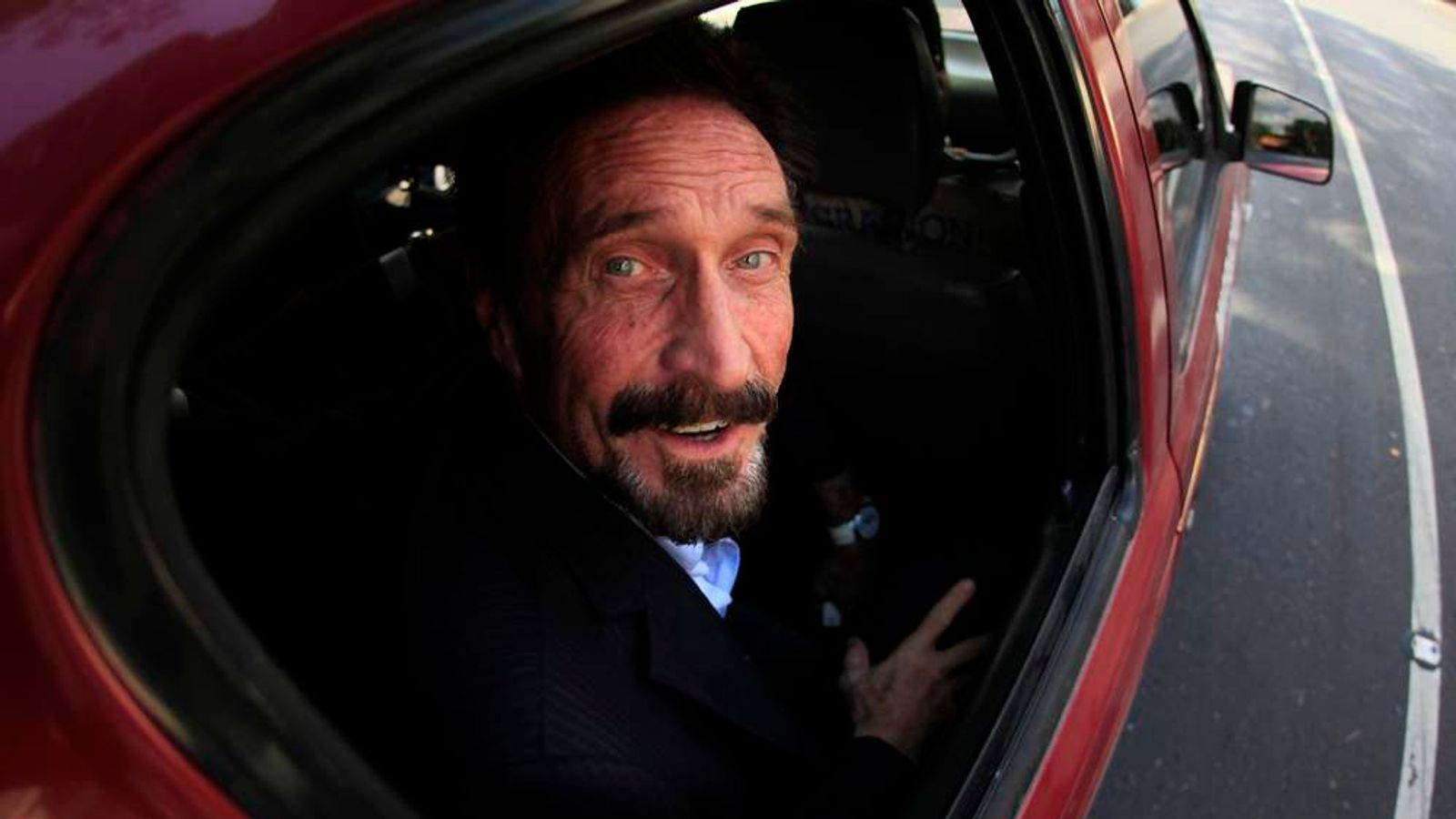 Software pioneer John McAfee is escorted by immigration officers to the Guatemalan Airport in Guatemala City
