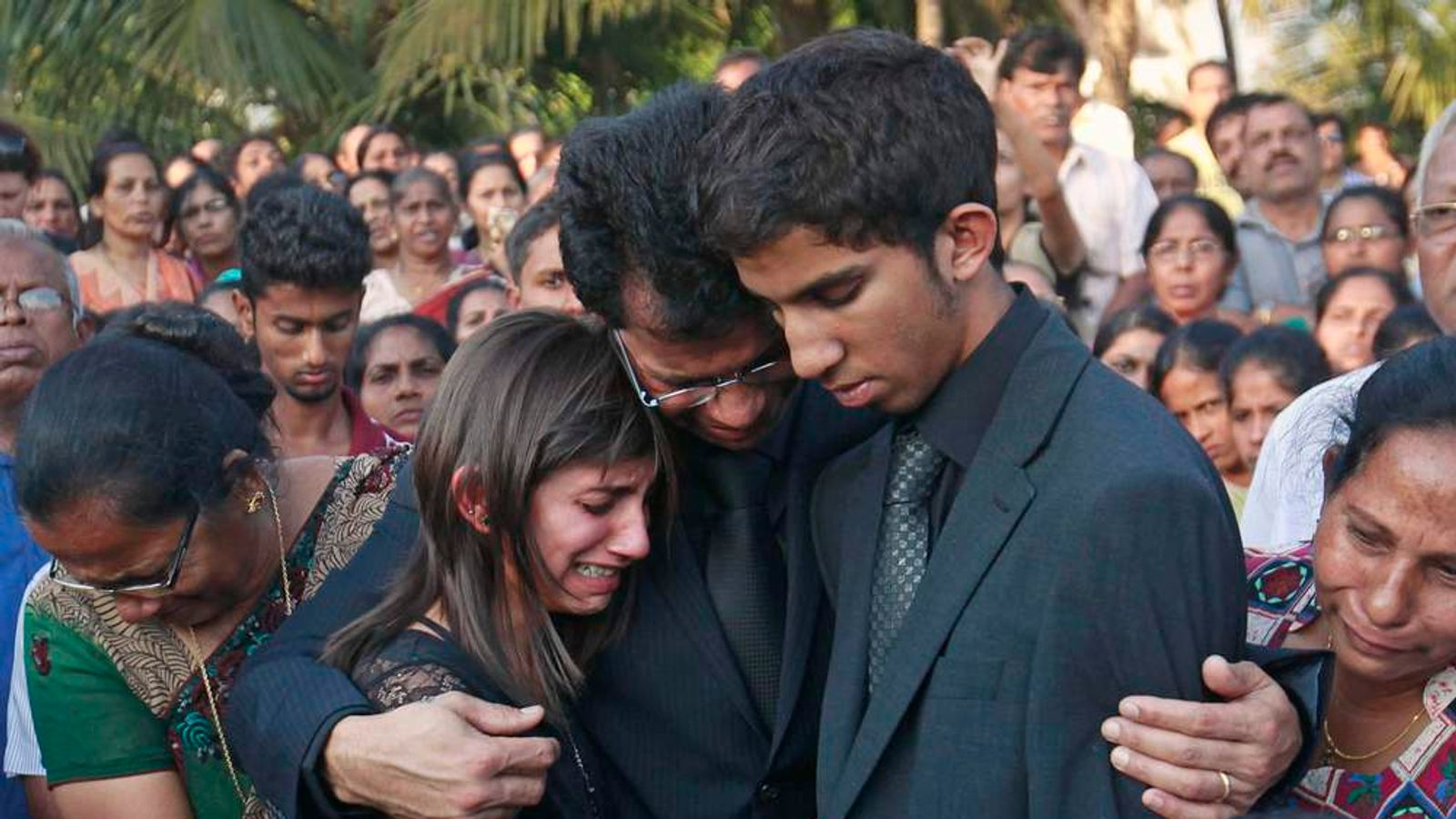 Jacintha Saldanha's widower Barboza and her children during her funeral at a cemetery in Shirva