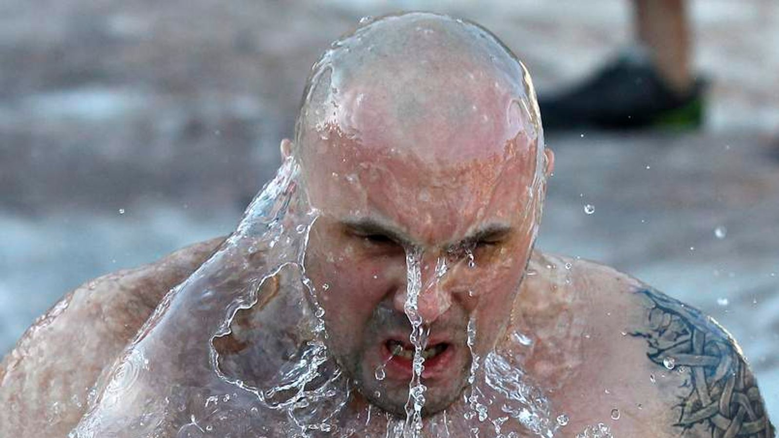 A man takes a dip in the icy waters of the River Neva in front  St. Isaac's Cathedral as part of celebrations to mark Epiphany