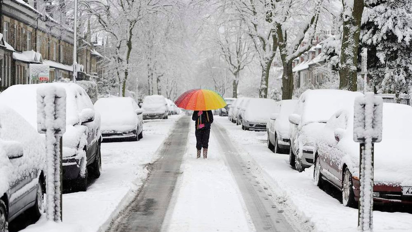 A girl walks along a snow covered street in Knaresborough