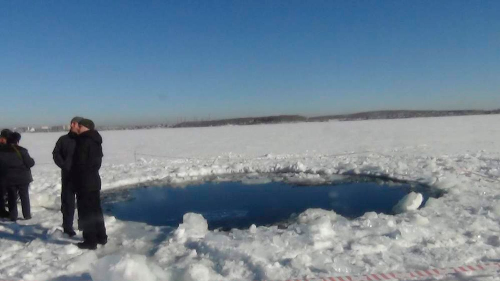 Russian police work near an ice hole at lake Chebarkul, said by the Interior Ministry department for Chelyabinsk to be the point of impact of a meteorite