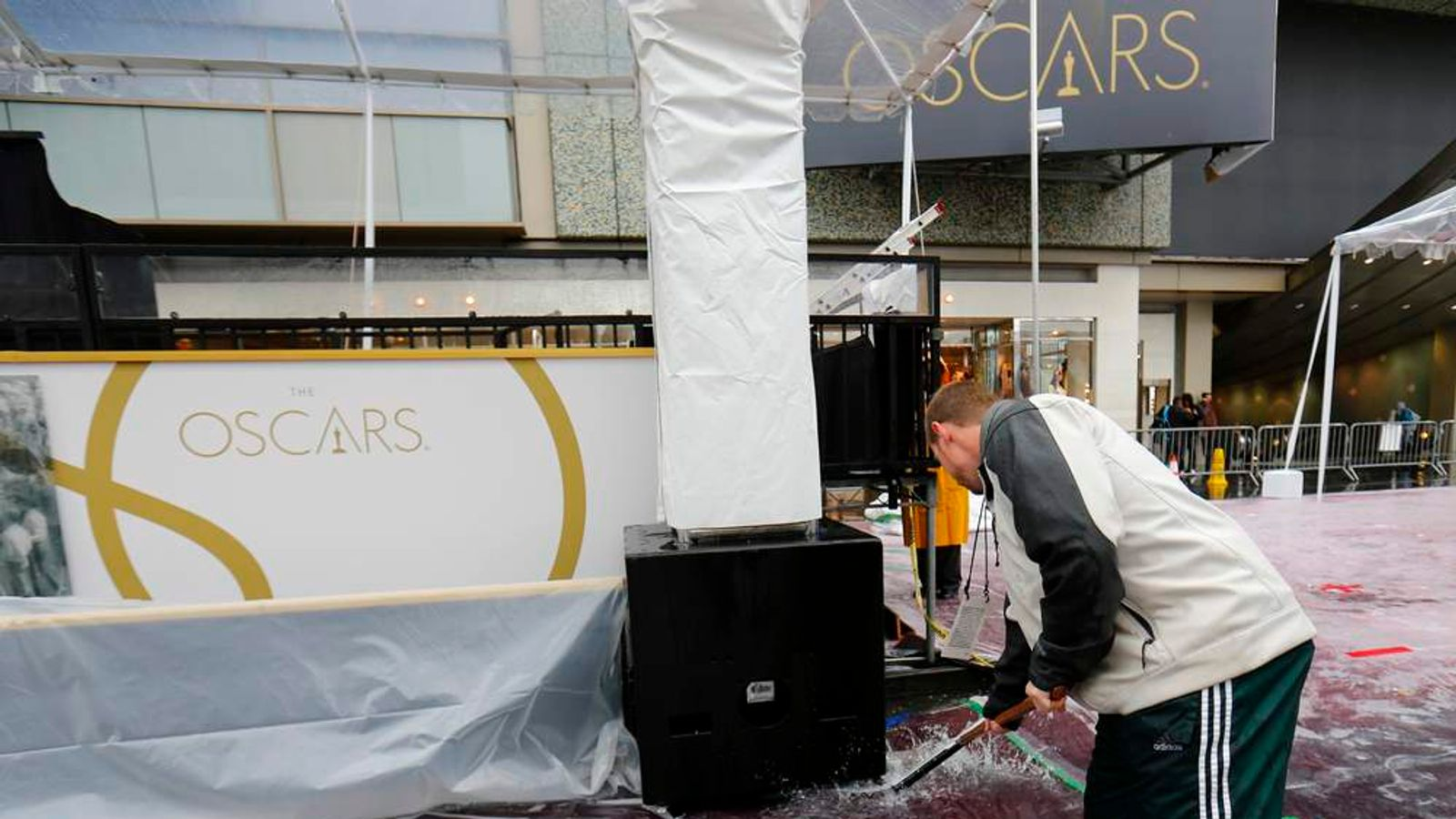 A worker pushes water off the red carpet as preparations for the 86th Academy Awards continues in the rain outside the Dolby Theatre in Hollywood