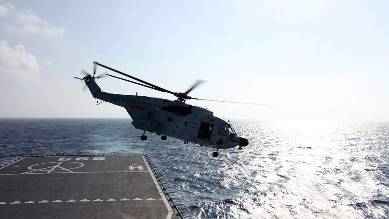 A helicopter takes off from Jinggangshan warship to search the waters suspected to be the site of the missing Beijing-bound Malaysia Airlines flight MH370.