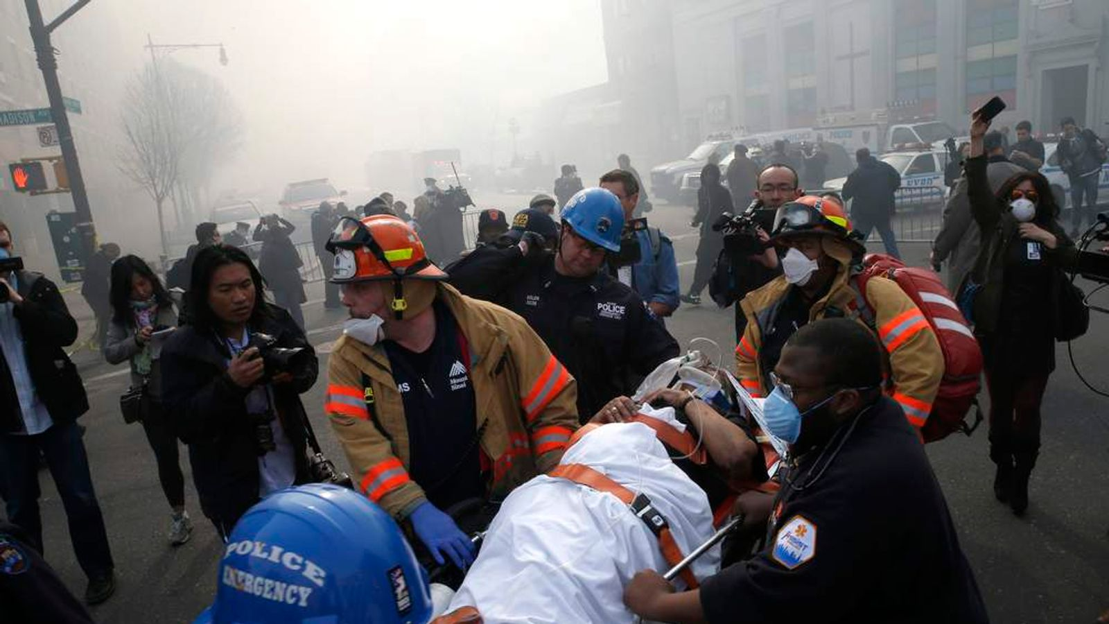 A victim is evacuated by emergency personal near an apparent building explosion fire and collapse in the Harlem section of New York City