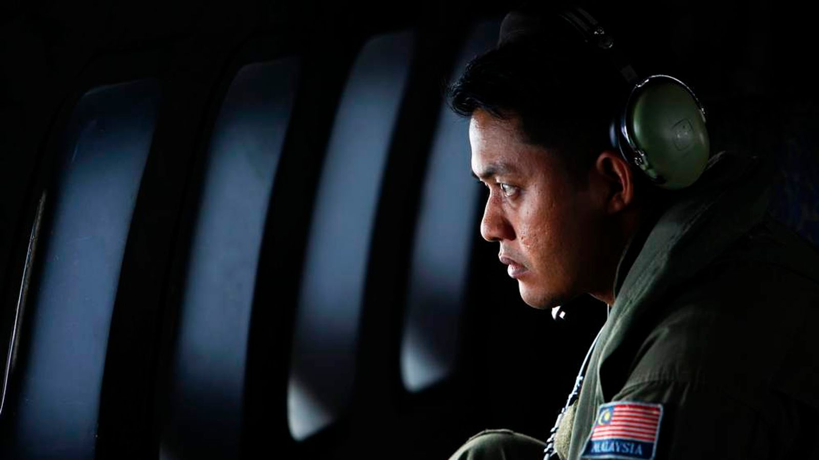 A crew member from the Royal Malaysian Air Force looks through the window of a Malaysian Air Force CN235 aircraft during a Search and Rescue operation to find the missing Malaysia Airlines flight MH370, in the Straits of Malacca