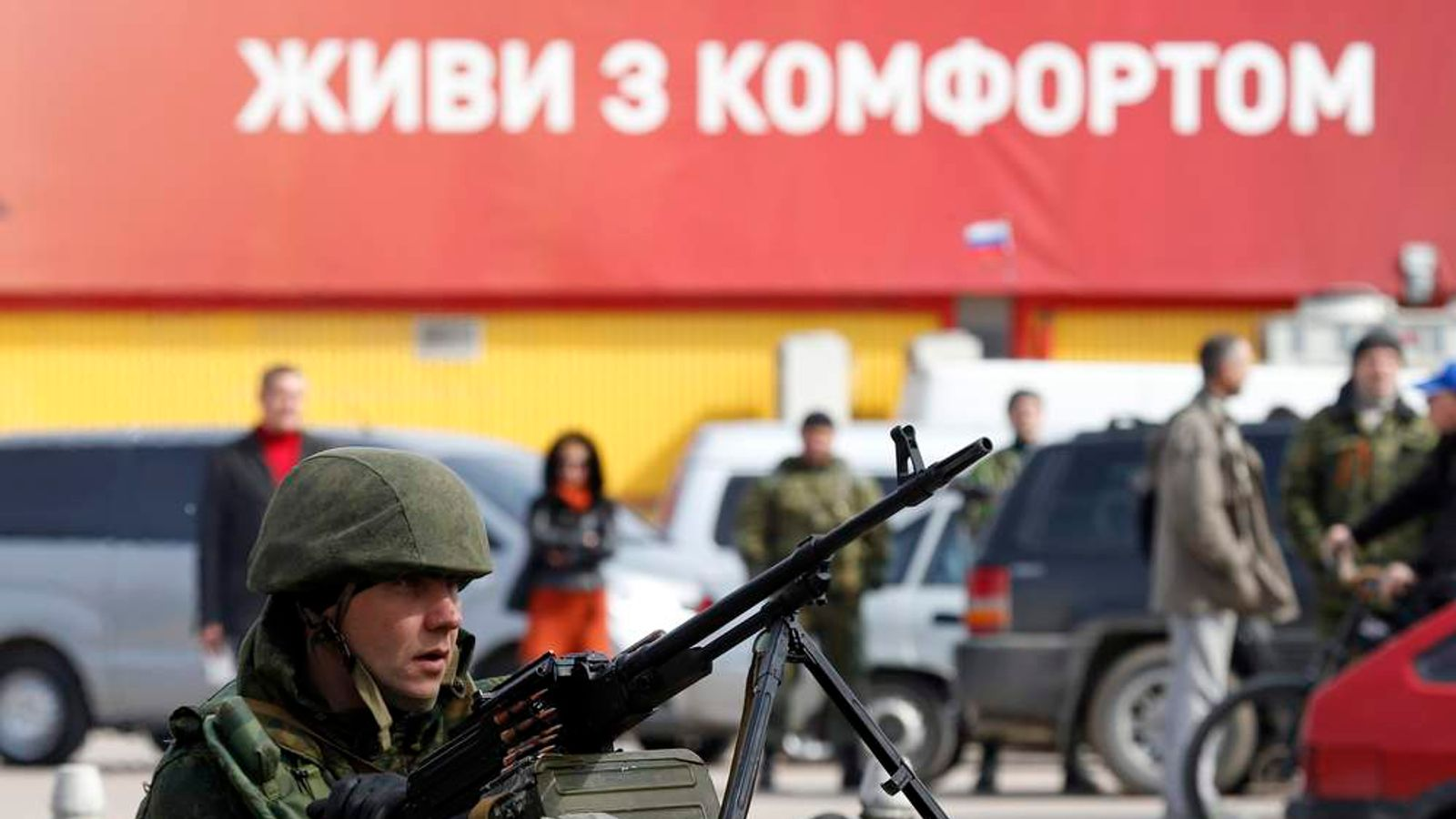 An armed man, believed to be a Russian serviceman, guards near the naval headquarters in Sevastopol