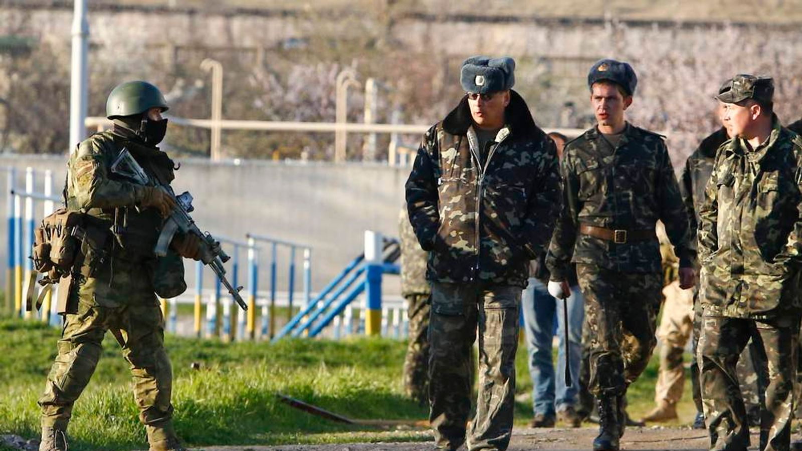 An armed man, believed to be a Russian serviceman, stands guard as Ukrainian servicemen pass by at a military airbase in the Crimean town of Belbek near Sevastopol