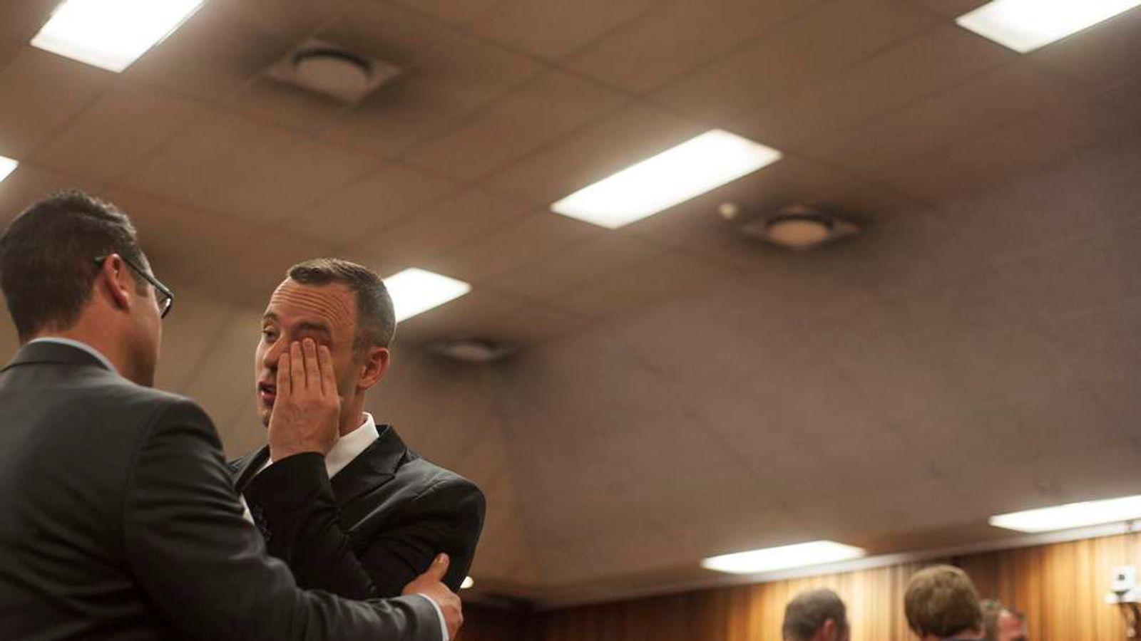 Olympic and Paralympic track star Oscar Pistorius greets his brother Carl in the North Gauteng High Court in Pretoria