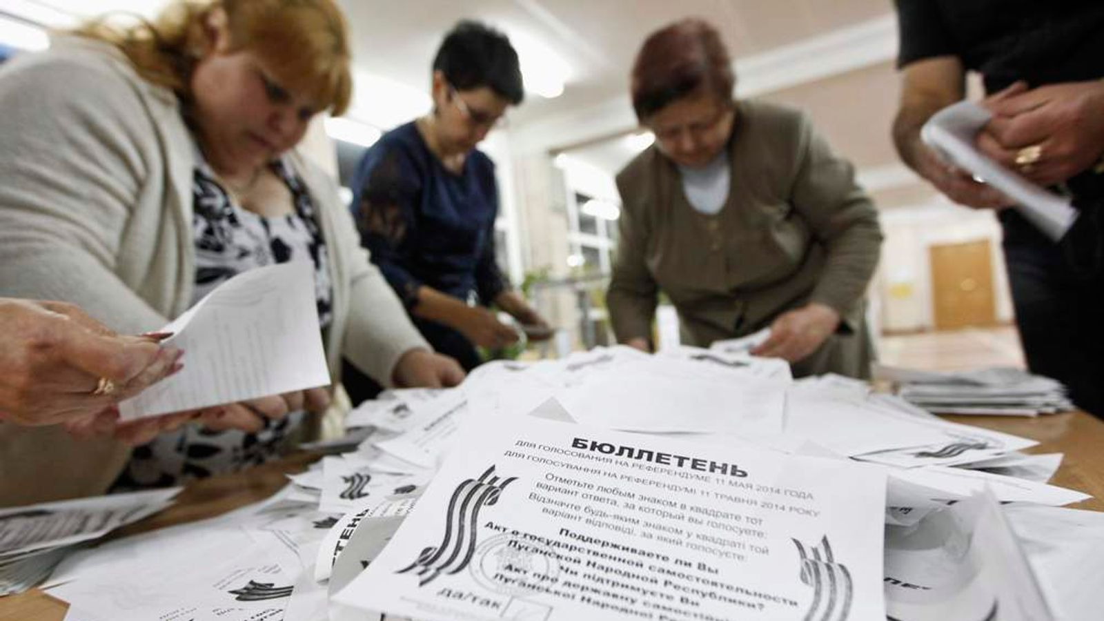 Members of local election commission empty ballot box as they start counting votes of today's referendum on status of Luhansk region in Luhansk