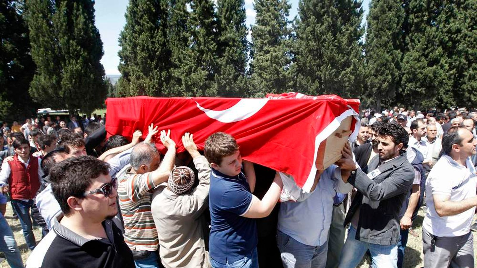 People carry the coffin of a miner who died in a fire at a coal mine, draped with a Turkish flag, during his funeral at a cemetery in Soma, a district in Turkey's western province of Manisa