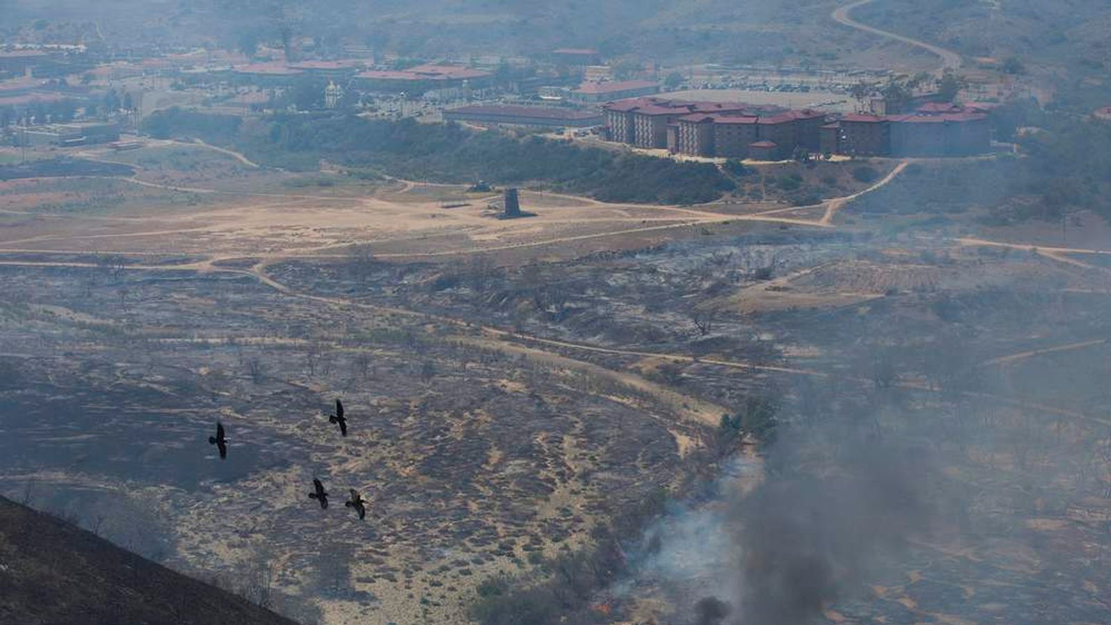 Birds fly past charred hills as the Talega Fire burns at Camp Pendleton