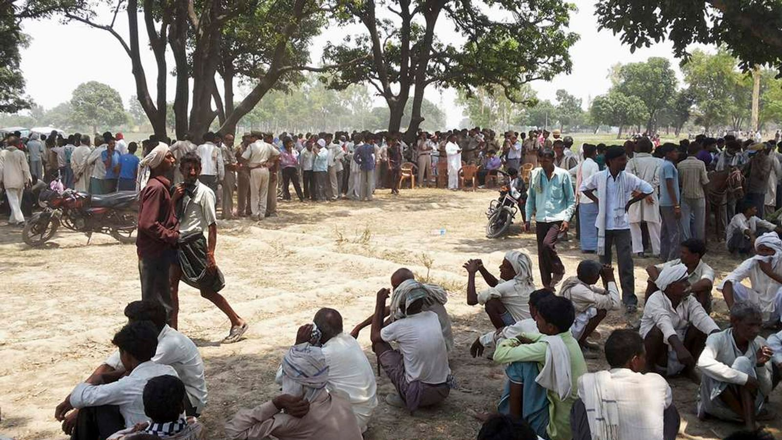 Onlookers sit at site where two girls were hanged from tree at Badaun district in Uttar Pradesh