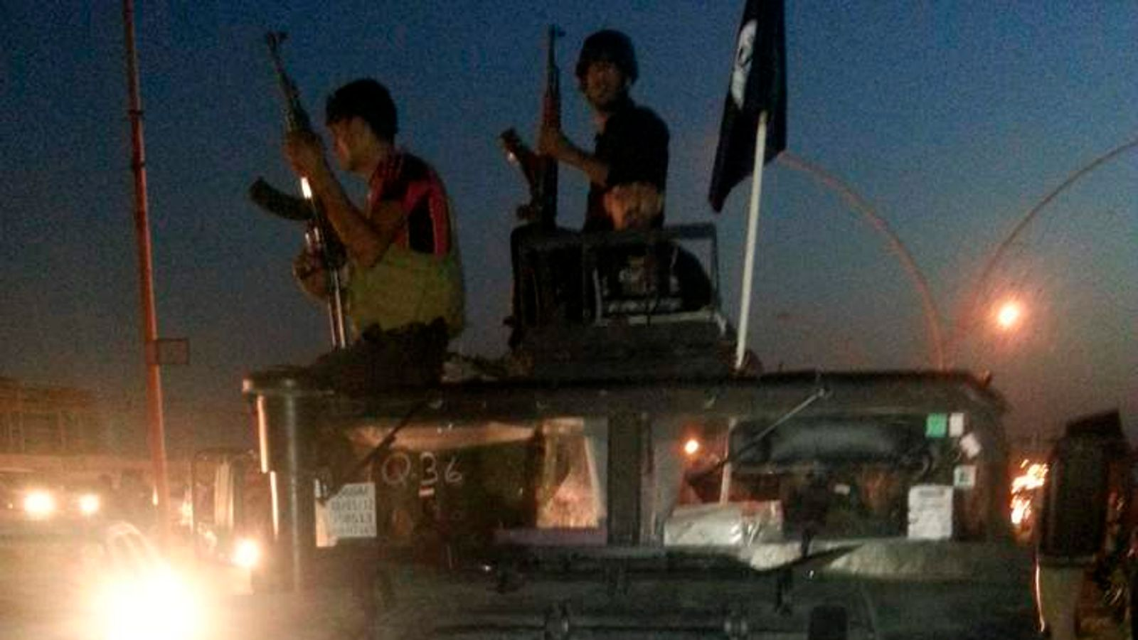 Fighters of the ISIL celebrate on a vehicle in Mosul