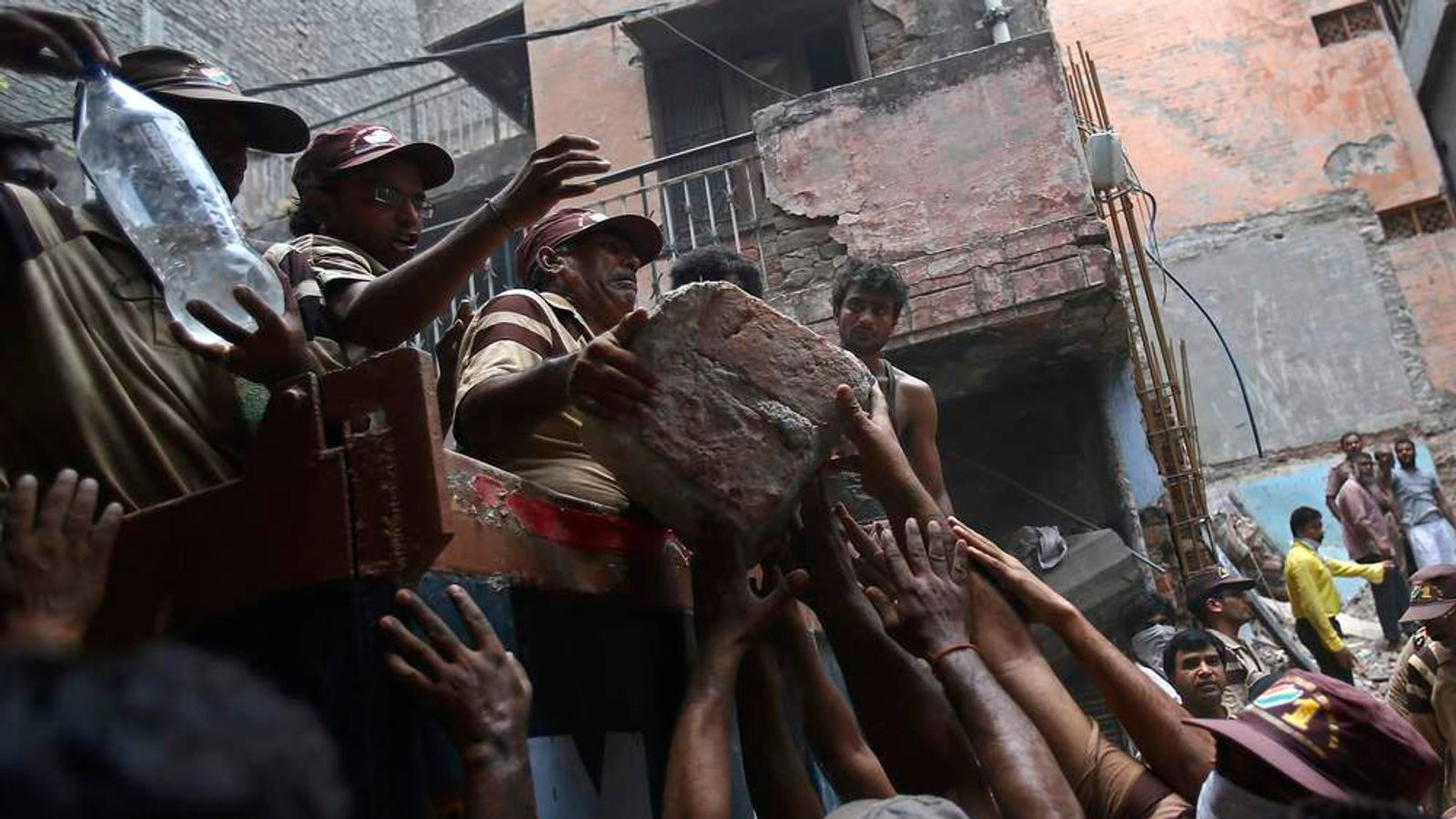 Rescue workers and volunteers load debris onto a truck at the site of a collapsed building in New Delhi