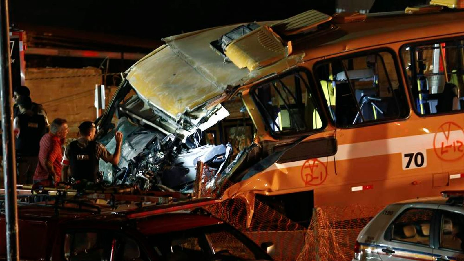 Police inspect a bus trapped underneath a bridge that collapsed while under construction in Belo Horizonte.
